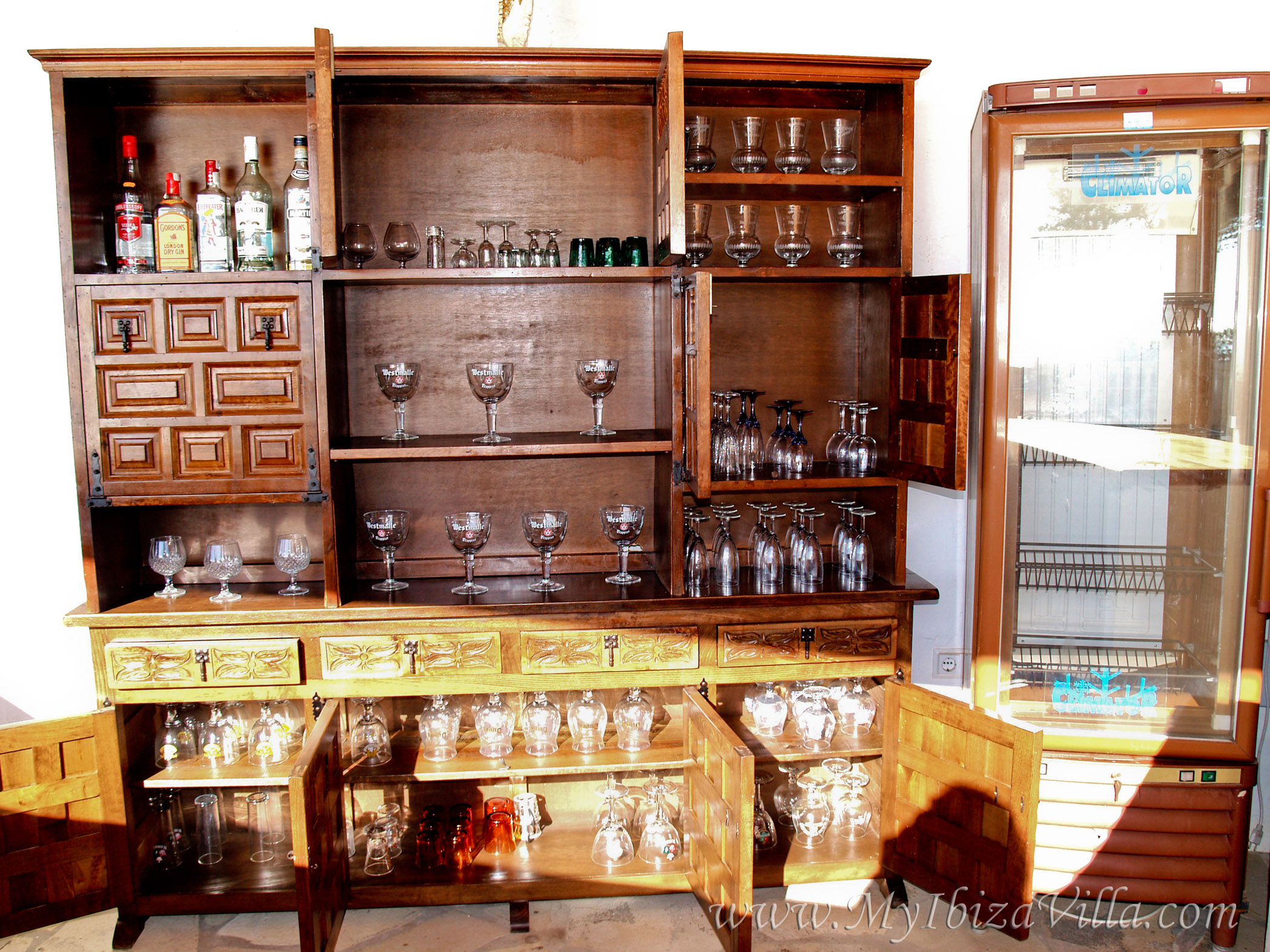 Cupboard with great variety of glasses behind the bar.